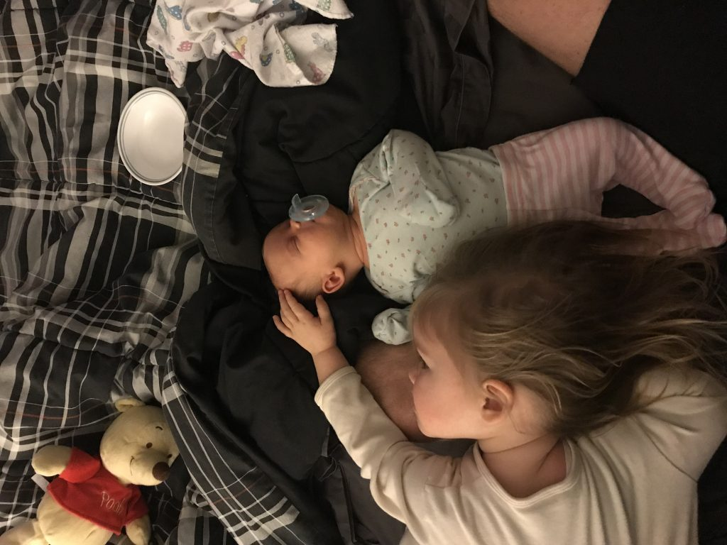 big sister cuddling with her new baby sister