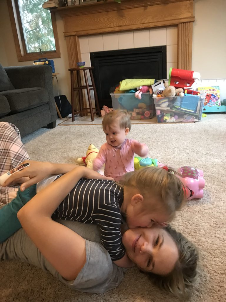 Byron is laying on mom giving her a kiss while Isla smiles in the background.