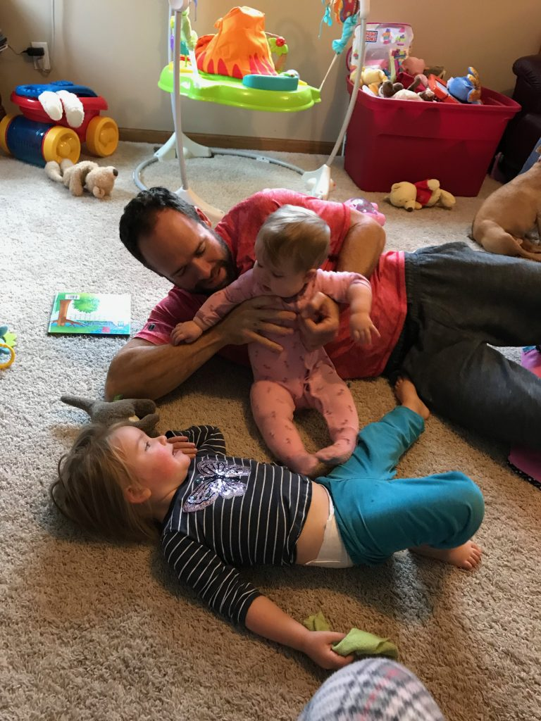 Daddy on the floor with both girls playing.