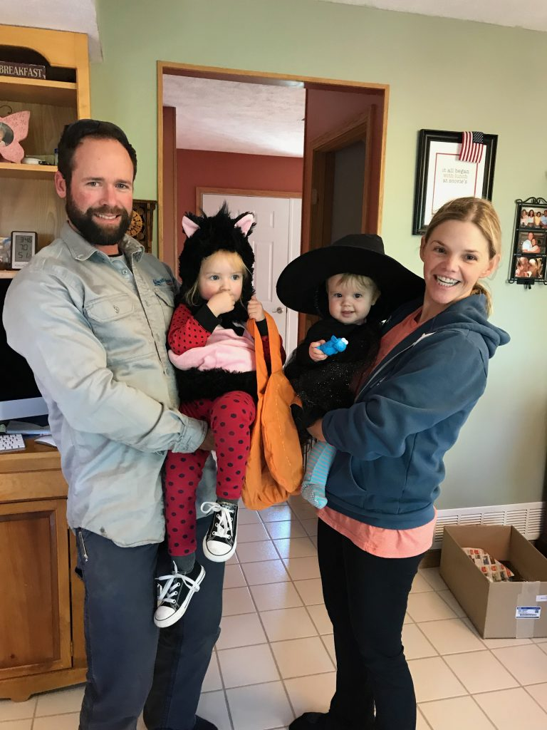 Mom and dad with a family photo holding both girls dressed in their halloween costumes.