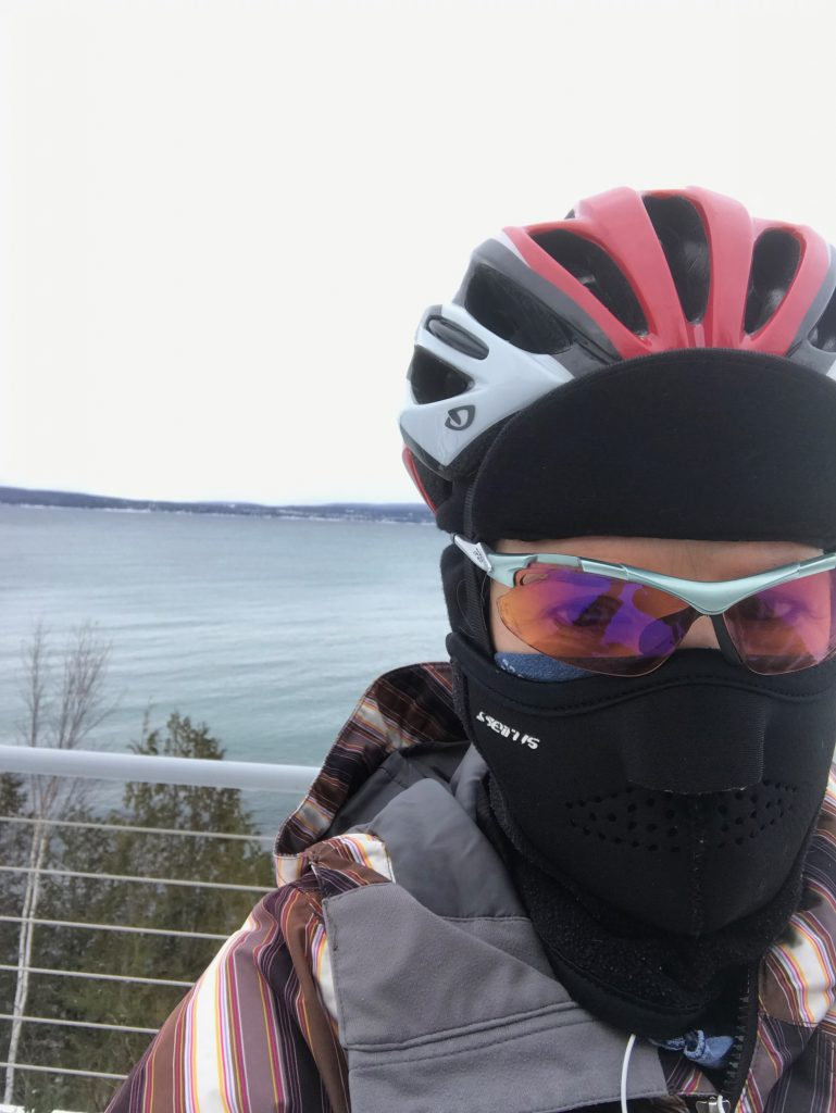 Jaime biking by the water in the winter wearing all the snow gear.